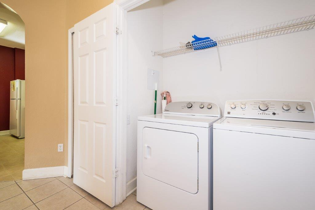 Washer and dryer provided in the set of double doors in the hallway by the front door.