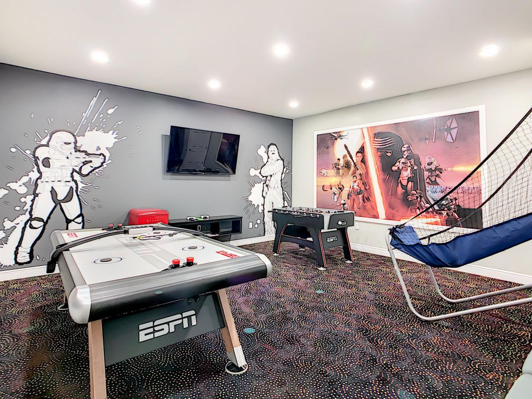 "Star Wars themed game room with a 65"" Roku TV, table games and Playstation 4."