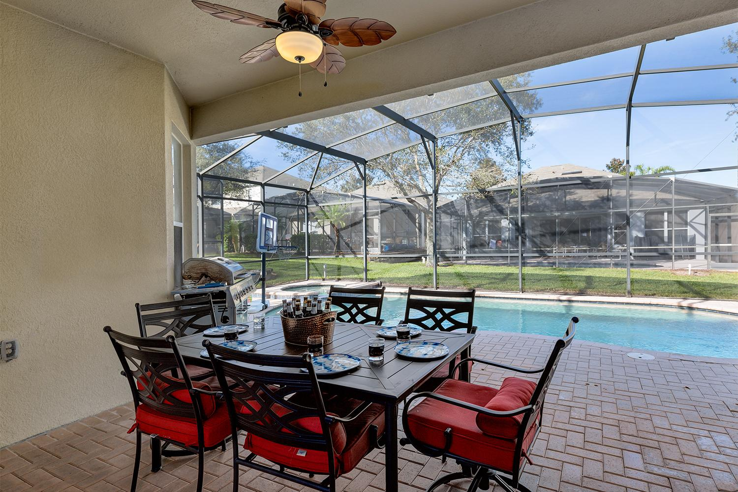 Outdoor dining area in the covered lanai overlooking the private pool.